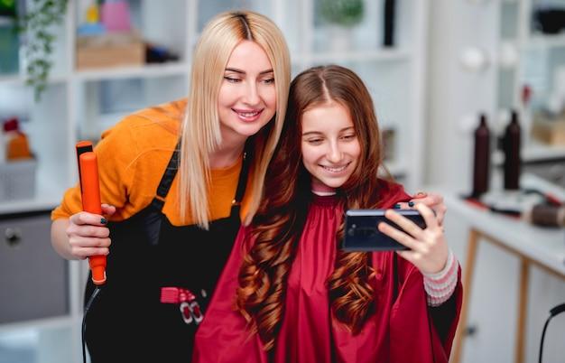 Selfie blond kobieta fryzjerka z klientem piękna modelka po profesjonalnej fryzurze loki