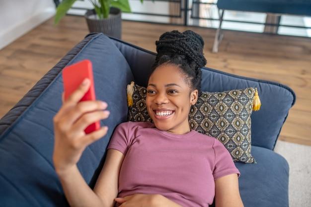 Selfie. ciemnoskóra śliczna młoda kobieta z fryzurą w tshirt z zębatym uśmiechem patrząc na ekran smartfona trzymając w wyciągniętej dłoni