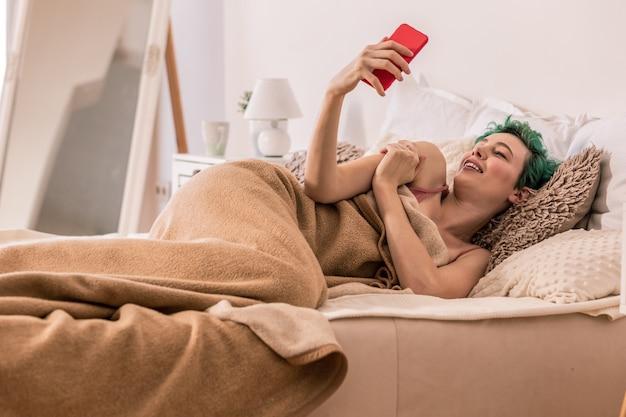 Selfie dla chłopaka. młoda zielonowłosa kobieta robi selfie dla chłopaka leżąc w łóżku