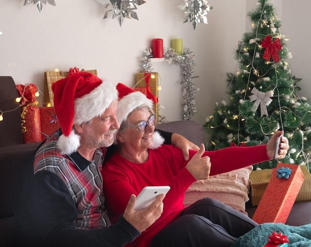 Selfie dla przyjaciół. starsza para mężczyzna i kobieta w kapeluszach świętego mikołaja siedząca blisko świątecznych prezentów.