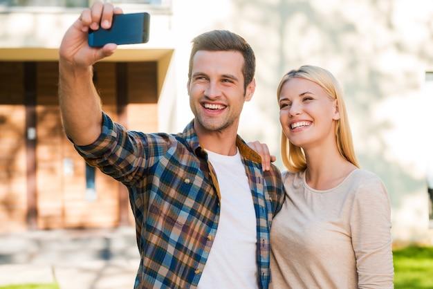 Selfie do ich rodzinnego albumu. wesoła młoda para łącząca się ze sobą podczas robienia selfie za pomocą smartfona, stojąc przed swoim nowym domem