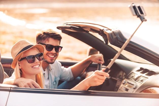 Selfie do zapamiętania dnia. szczęśliwa młoda para korzystająca z monopodu podczas robienia selfie w swoim kabriolecie