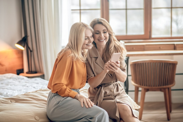 Selfie. dwie uśmiechnięte blondynki siedzące na łóżku i robiące selfie na smartfonie