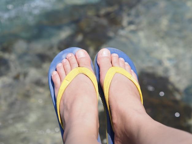 Selfie gołe stopy na sobie kolorowe sandały na tle wody morskiej