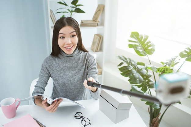 Selfie kobiety siedzącej przy stole i trzymającej w ręku dziennik