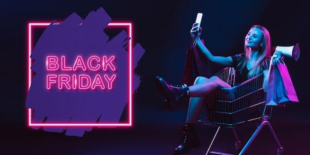 Selfie, megafon. portret młodej kobiety w neon na ciemnym tle studio. ludzkie emocje, czarny piątek, cyber poniedziałek, zakupy, sprzedaż, koncepcja finansów. miejsce. bezszwowy post na instagram.