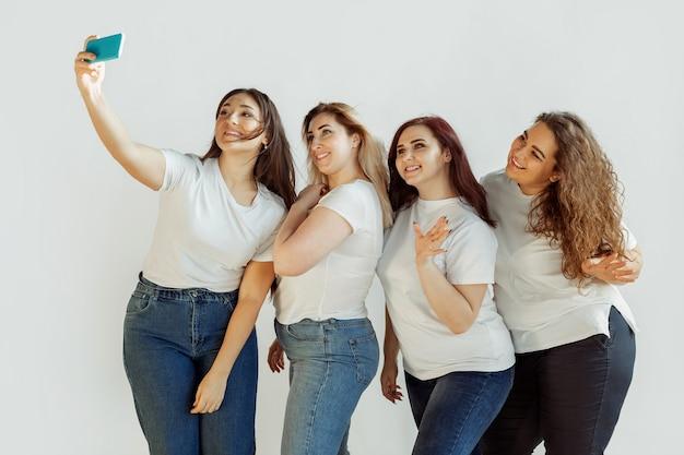 Selfie. młode kobiety rasy kaukaskiej w ubranie, wspólna zabawa. przyjaciele pozujący na białym tle i śmiejący się, wyglądają na szczęśliwych, zadbanych. pozytywne ciało, feminizm, kochanie siebie, koncepcja piękna.