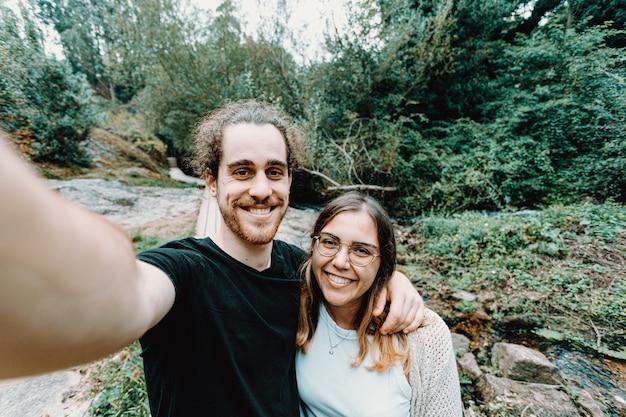 Selfie młodej pary podającej bis do kamery w lesie