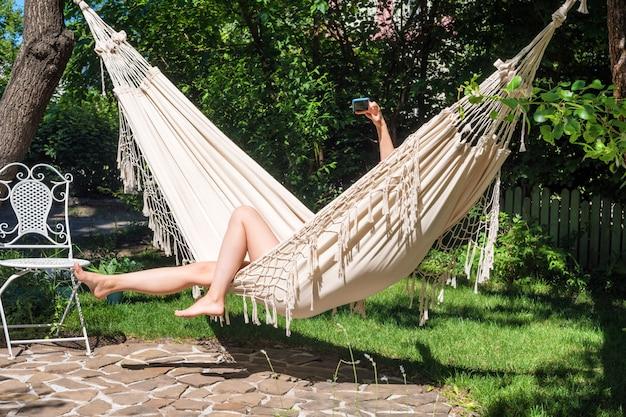 Selfie na wakacje. cieszyć się latem. młoda kobieta używa smartphone kłaść w hamaku w ogródzie