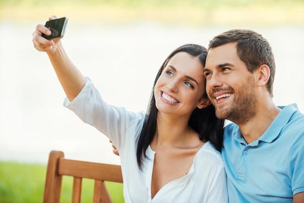 Selfie! piękna młoda kochająca para siedzi razem na ławce i robi selfie z telefonem komórkowym