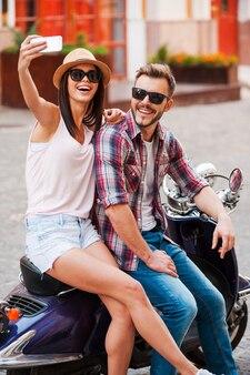 Selfie! piękna młoda kochająca para siedzi razem na skuterze i robi selfie za pomocą smartfona