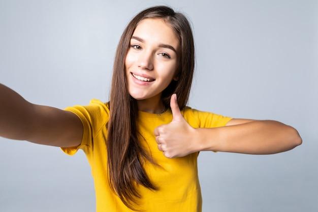 Selfie pokazuje kciuk szczęśliwy i mrugać odizolowywającymi na biel ścianie szczęśliwa kobieta
