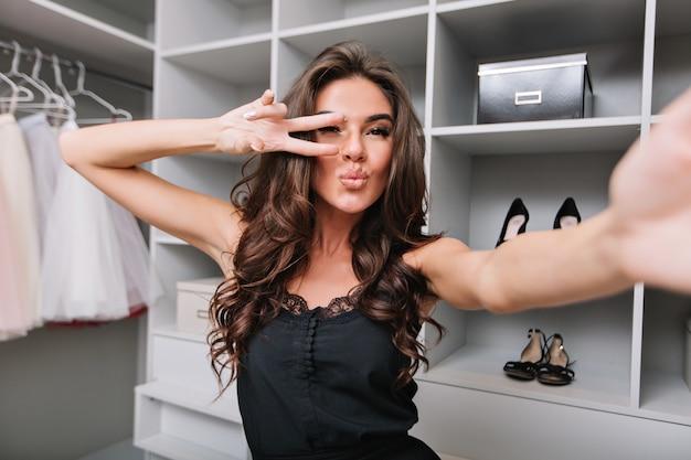 Selfie-portret młodej kobiety z brunetką, stojącej w luksusowej garderobie i robienia selfie. wysyła buziaka. ubrana jest w elegancką czarną sukienkę.