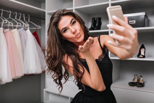 Selfie-portret pięknej brunetki robi selfie za pomocą smartfona w jej garderobie. wysyła buziaka. jej stylowe ubrania, wyrażające prawdziwe pozytywne emocje na twarzy.
