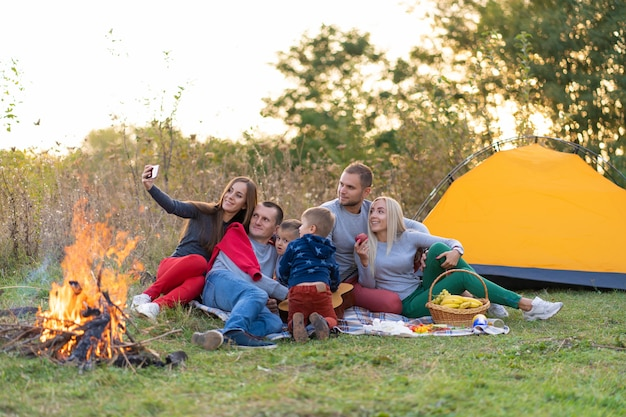 Selfie przyjaciół z natury. przyjaciele odpoczywają w pobliżu jeziora. świetna zabawa. duża rodzina zebrała się na wakacjach. dzieci i rodzice na pikniku w letnim lesie.