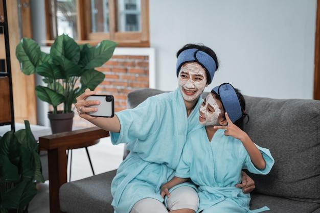Selfie razem z matką i małą dziewczynką wykonaj maseczkę na twarz z ręcznikiem na głowie