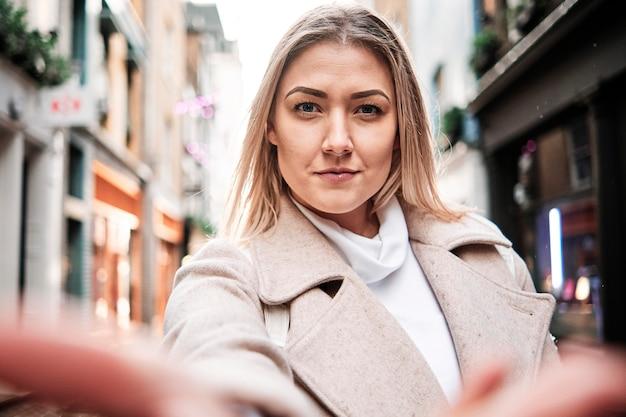Selfie szczęśliwej uśmiechniętej blondynki na ulicy. wideo rozmowa.