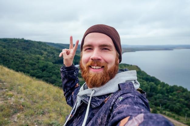 Selfie turysta brodaty rudowłosy mężczyzna turysta w kapeluszu biorąc autoportret nad jeziorem. mężczyzna backpacker uśmiecha się do aparatu w telefonie na przygodę natura podróż.