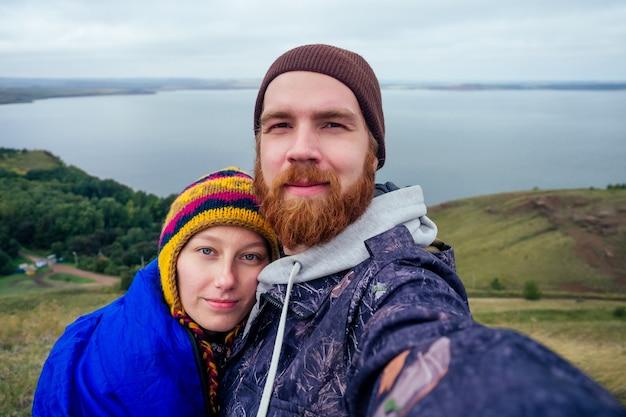 Selfie turysta rudowłosy brodaty mężczyzna turysta w kapeluszu z ukochaną kobietą robi autoportret nad jeziorem. para zakochanych backpacker uśmiechając się do aparatu w telefonie na przygodę natura podróż.