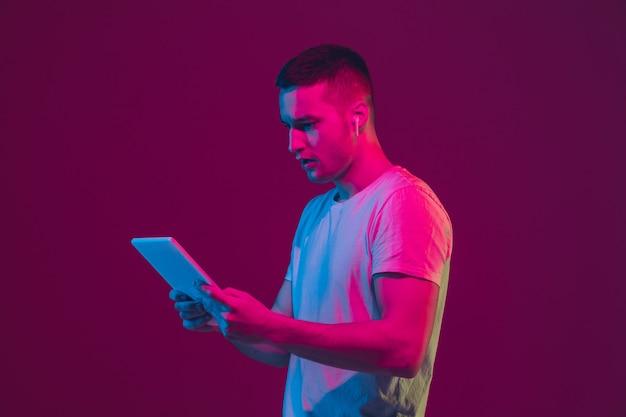 Selfie, vlog, zakupy, zakłady. portret mężczyzny kaukaski na białym tle na ścianie studio różowo fioletowy.