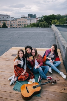 Selfie w spotkaniach z bliskimi przyjaciółmi. uśmiechnięte dziewczyny z fast foodami robią autoportret smartfonem, niezwykłe miejsca do odpoczynku i komunikacji, wspólne spędzanie czasu, koncepcja wesołej i radosnej atmosfery
