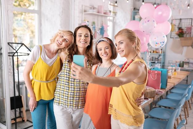 Selfie z przyjaciółmi. blondynki kobieta ubrana w modną żółtą bluzkę robienie zdjęć z przyjaciółmi