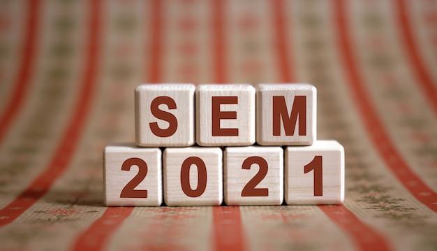 Sem 2021 tekst na drewnianych kostkach na monochromatycznym tle z odbiciem.