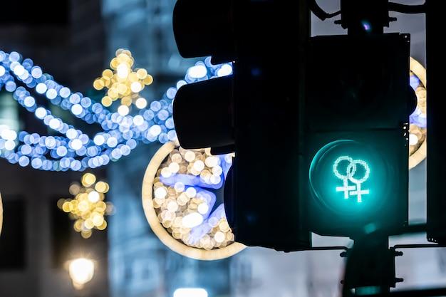 Semafor dla pieszych z zielonym światłem i niewyraźnymi świątecznymi dekoracjami ulicznymi