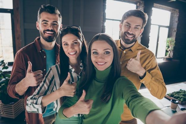 Seminarium coachingowe dotyczące budowania zespołu. cztery osoby mężczyźni kobiety lubią osiągać korporacyjny klimat cel, aby selfie pokazać kciuk w górę dobry symbol nosić sweter koszula na stanowisku pracy