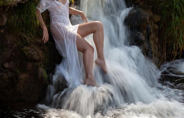 Seminude młoda kobieta w białej sukni cieszy się świeżością i chłodem w strumieniach wody wodospadu