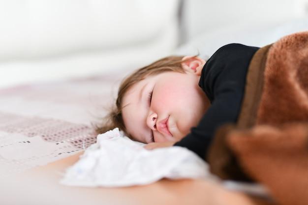 Sen dziecka w ciągu dnia. zdrowy sen w ciągu dnia dla noworodka. dziecko śpi w dziecięcym kokonie na łóżku. odpoczynek dziecka po aktywnej zabawie z rodzicami
