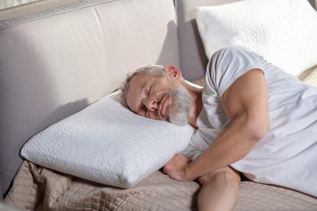 Sen w ciągu dnia. dorosły brodaty mężczyzna w białej czapce z zamkniętymi oczami leżąc na łóżku