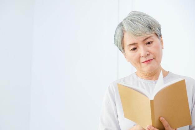 Senior asia kobieta czyta książkę na białym tle.