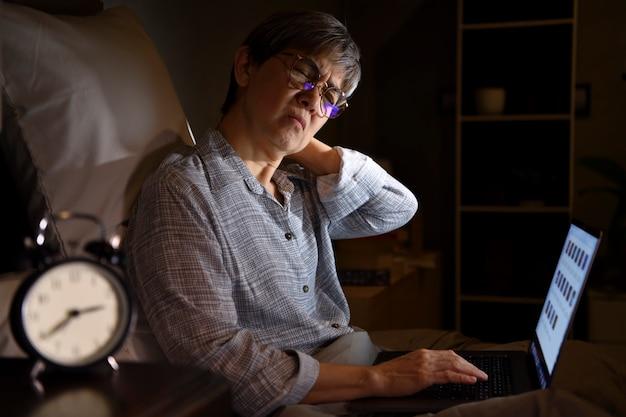Senior asian kobieta z bólem i bólem mięśni od używania laptopa w łóżku