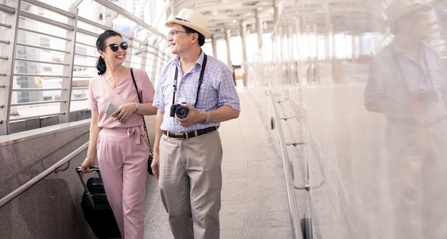 Senior azjatyckich para z kobietą, przeciągając walizkę i szczęśliwie rozmawiając z uśmiechem na lotnisku, aby przygotować się do podróży.
