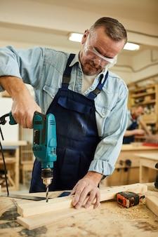 Senior carpenter drilling wood