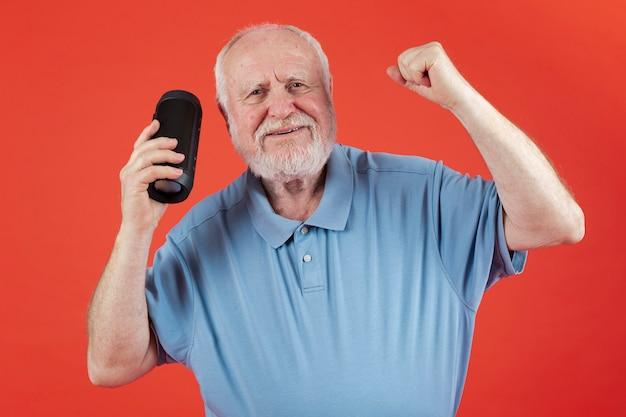 Senior cieszący się muzyką odtwarzaną na głośniku