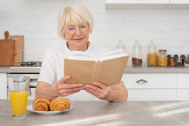 Senior czyta książkę w kuchni