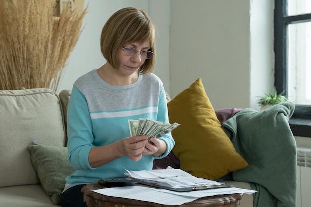 Senior dojrzała kobieta za pomocą kalkulatora trzymając papierowy rachunek obliczania podatku budżetowego pieniędzy