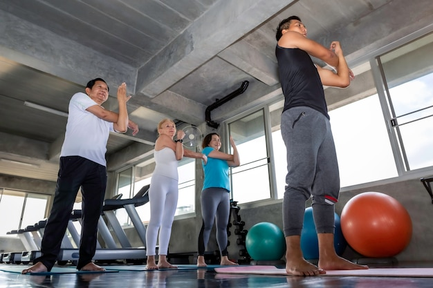 Senior grupy atrakcyjne rozciąganie na siłowni fitness.