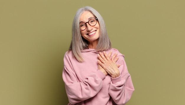 Senior kobieta czuje się romantyczny, szczęśliwy i zakochany, uśmiecha się radośnie i trzyma ręce blisko serca