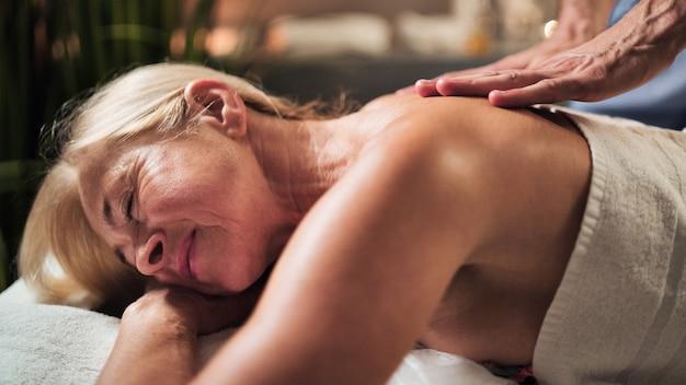 Senior kobieta o masaż pleców w spa.