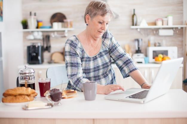 Senior kobieta pije kawę i pracuje na laptopie w kuchni podczas śniadania. osoba w podeszłym wieku na emeryturze, pracująca w domu, pracująca zdalnie przy użyciu zdalnej komunikacji internetowej o pracy online na nowoczesnych technologiach