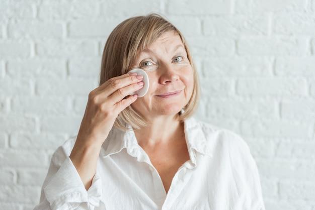 Senior kobieta przeciwstarzeniowy balsam przeciw cieniom pod oczami