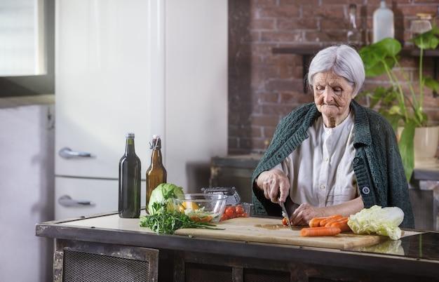 Senior kobieta siekanie świeżych warzyw na sałatkę. zdrowe nawyki żywieniowe.