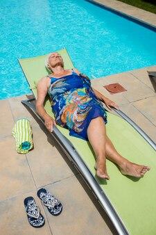 Senior kobieta śpi na fotelu przy basenie