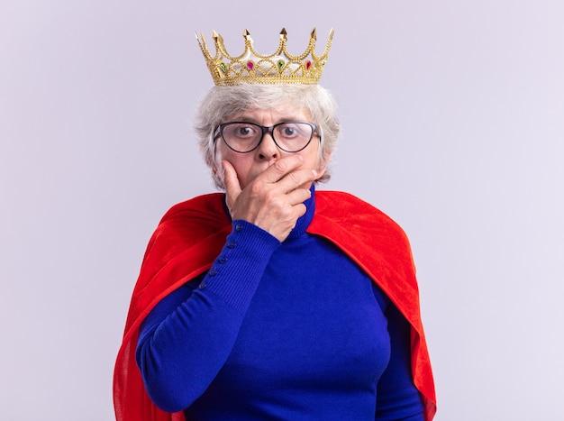 Senior kobieta superbohater ubrany w czerwoną pelerynę i okulary z koroną na głowie patrząc na kamerę będąc w szoku zakrywając usta ręką stojącą na białym tle
