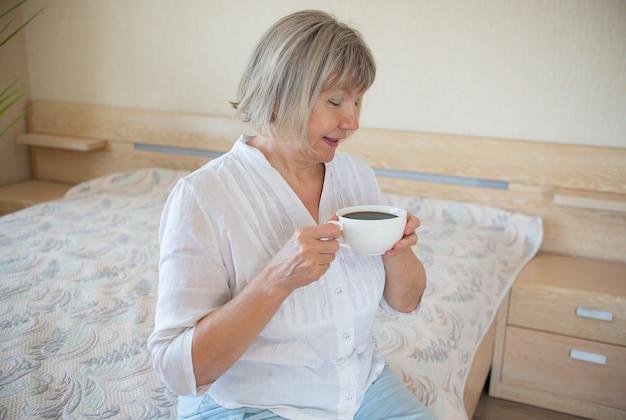 Senior kobieta trzyma kubek kawy relaks uśmiechający się w swoim domu w sypialni. dzień dobry koncepcja, obudź się