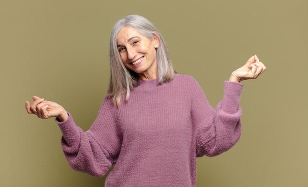 Senior kobieta uśmiechnięta, beztroska, zrelaksowana i szczęśliwa, tańcząca i słuchająca muzyki, bawiąca się na imprezie