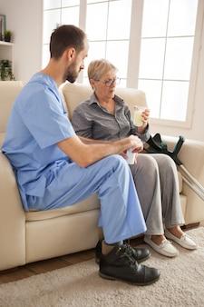 Senior kobieta w domu opieki biorąc jej lek. mężczyzna lekarz.